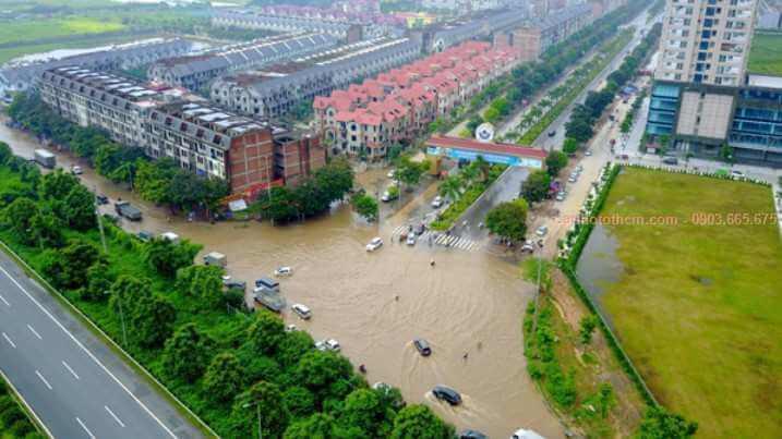 Đoạn đường trước cổng khu Thiên Đường Bảo Sơn giáp Đại lộ Thăng Long ngập sâu sau cơn mưa sáng 13/7 khiến người dân đi lại khổ sở